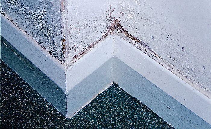 Voet van een binnen muur gelijkvloers. Boven plinten zoutkristallen en schimmelvlekken door vocht.